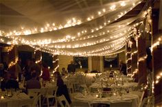 Christmas lights hung in tulle. What a lovely way to light your party!