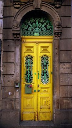 I love how tall and narrow these double yellow doors are! And the beautiful green iron scroll work in the windows and fanlight makes the whole thing pop right out of the grey facade! Cool Doors, The Doors, Unique Doors, Windows And Doors, Beautiful Front Doors, Door Knockers, Door Knobs, Door Handles, When One Door Closes