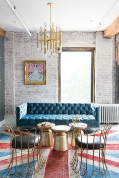A modern take on the classic chesterfield sofa from ModShop is accented by a trio of gold West Elm side tables.
