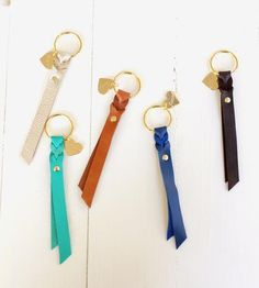 This isn't your regular ol' leather key fob. Each key chain is handcrafted with soft leather, woven to create the braided detail near the ring and finished with a single stud. It's attached to a golden key ring with a dainty heart charm, for a ladylike take on the leather keychain.