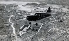 """""""Grasshopper"""" Over Naha, Okinawa—A Marine observation plane flies low over Naha, capital of Okinawa, during the Battle of Okinawa, 1945. On this flight, the tiny ship drew small-arms and antiaircraft fire from the city, which was in Japanese control. Note the sunken shipping in the harbor in the background."""