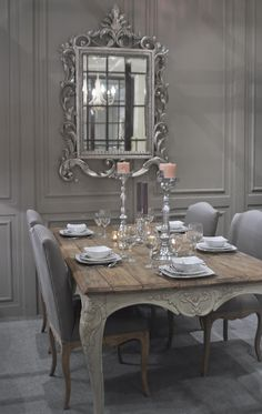 Charming shabby chic dining room in French Grey with an excuisite carved French mirror as art on the wall.
