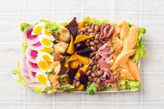 """A composed summer salad- From the French """"salade composée,"""" a composed salad is simply salad arranged on a plate rather than tossed in a bowl.  It shows off the intense, irresistible vegetables, herbs and fruits of the season — but can also have rich components like cheese, eggs, toasted nuts and smoked fish or meat. With a loaf of (preferably grilled) bread, it is a meal in itself."""