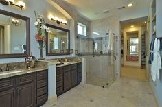 Blue bathroom with rich brown cabinets and gorgeous stone countertops