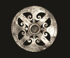 A flat discoid phalera with cruciform spokes and interstitial trefoil scrolls, concentric ring.