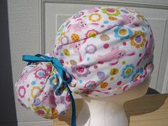 $13.99 This scrub hat is has SILLY PINK EASTER BUNNIES HOPPING all over it surrounded by DECORATED EASTER EGGS and SPRINGTIME FLOWERS. It i...