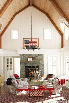 In designer Chipper Joseph's Idaho house, the great room offers a comfortable atmosphere. The restrained design allows the antique flag and vintage-inspired furnishings in red, white, and blue to shine.