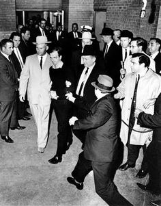 The accused assassin of President John F. Kennedy, Lee Harvey Oswald, center in handcuffs, is escorted to the Dallas city jail as nightclub owner Jack Ruby, foreground, approaches Oswald with a pointed revolver in the underground garage of the Dallas police headquarters, Texas, Nov. 24, 1963. Seconds later Ruby shot Oswald in the stomach.