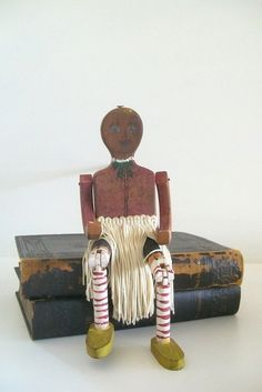 Shes great! A folk art wooden jig doll/puppet that has very detailed painting from her face to her bow, to her thigh shot. She wears a white