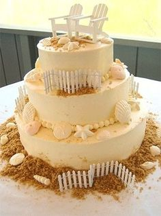 beach wedding cake - you could do just one layer for a pretty birthday cake. Love the graham cracker crumbs, shells, chairs, fence and sand-colored frosting.