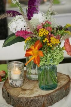 Rustic wildflower centerpieces on wood slab