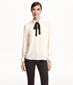 Gently flared blouse in woven crêpe fabric. Collar with attached bow at neck, concealed buttons at front, and long puff sleeves with wide cuffs with button. Yoke at back.