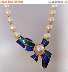 This #vintage pearl and blue green enamel bow necklace is absolutely stunning!  It features single large faux pearl strand with a gold tone blue green enamel bow enhancer/fa... #ecochic #etsy #jewelry #jewellery