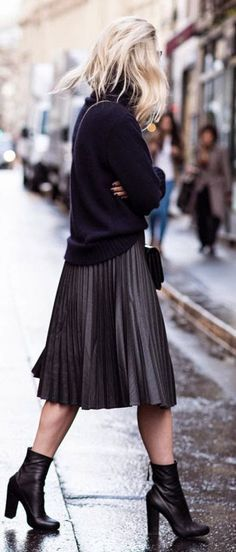 pleated midi skirt and ankle boots with an oversized knit.