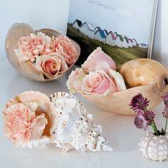 Un bouquet contenant des oeillets, des roses et des Astrantia dans des coquillages