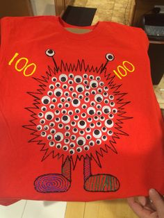 "Simple project for 100th day of school. I used fabric markers to draw my ""monster"", fabric glue pen + googly eyes, fabric paint that dries puffy to finish it off. I also placed a piece of cardboard between the layers of the shirt to not get glue/paint on the back side. Took me & my 5 yr old an hour to complete (including counting out the 100 eyes)."