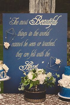 Vista valley country club wedding photo shoot blue sign with gold calligraphy writing and white and green flowers on top of black and gold stand with gold decor and blue and white wedding cakes on table with white and gold patterned table cloth linen