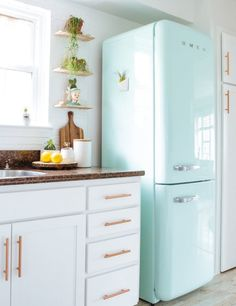 This Stylish Kitchen Trio Will Live Happily Every After | Done right, it's a beautiful thing that elevates all involved, as this one particular kitchen combo proves. Retro pastel fridges (like these iconic Smeg refrigerators), white cabinets, and metallic hardware form a happy perfect union that will never break up, and will never go out of style.