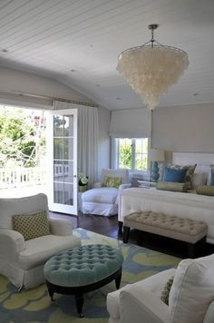 Fresh master bedroom with a shell chandelier and a french door leading to the balcony by Brooke Giannetti.