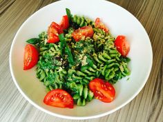 Spinach pasta. Rice fuselli in sauce made from blended spinach, soya milk, olive oil and pine nuts, with olives, capers and vine tomatoes, sprinkled with nutritional yeast