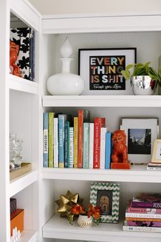 Beautifully styled bookshelves with vintage style white decanter, silver bowl and framed art work. The middle shelf houses a colorful array of books held up with red Foo dog. Layered behind is a framed photograph and smaller framed art piece. On the bottom shelf is a brass geometric sculpture, chevron green and ivory inlaid frame and small trinket box turned vase.