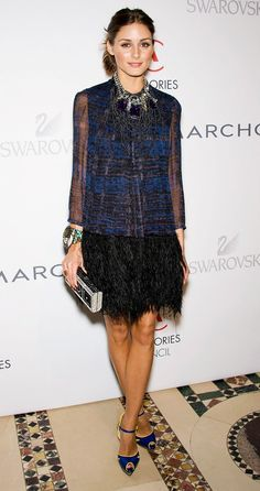 2010: Olivia Palermo wears a black and blue mini dress with feather detailing, ankle-strap heels, statement jewelry, and a box clutch