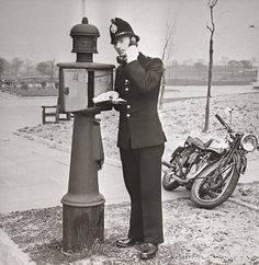 Another classic image from the ongoing digitisation of the archives of the Greater Manchester Police Museum. A police officer telephones his station from a police pillar in a local park. No doubt the call had something to do in the motorcycle in the background, which looks a little worse for wear. We have no information about which force this officer served with or the date of the image. Can you help? www.gmpmuseum.co.uk