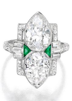 Platinum, Diamond and Emerald Ring. Set with two pear-shaped diamonds weighing approximately 4.75 carats, accented by baguette and square-cut diamonds weighing approximately .75 carat, further decorated with triangle-shaped calibré-cut emeralds, circa 1925.