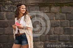 Longhaired hippy-looking young lady in jeans shorts, knitted shawl and white blouse standing near stone wall in old town and holding cell phone Jeans For Short Women, Knitted Shawls, Hippy, Old Town, Young Women, Jean Shorts, That Look, Hipster, Stock Photos