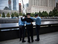 Zachary Ellicott, left, a firefighter in Stanhope, N.J., (left) and his brother Benjamin Ellicott, far right, also a firefighter in Stanhope, hug their father, Mitch Ellicott, a lieutenant with the Sussex County Sherrif's office as they take a moment to remember a family member lost in the terrorist attack in New York City.  Andrew Burton, Getty Images