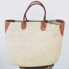 """Beautifully refined, artisanal made palm basket with cognac leather handle and details.  Size: 20"""" wide x 15.5"""" high x 10"""" deepHandmade in NigerPalm fiber and Leather*Pre-order for end of May delivery"""