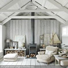 Ein schmaler Ofen gestaltet den Mittelpunkt des Raumes und wird von zwei niedrigen Holztischen eingerahmt, unter denen das Feuerholz gestapelt wird. Der gemütliche …