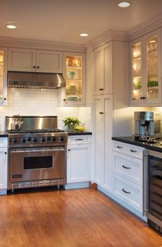 White kitchen with glass cabins and subtle relief of white doors and drawers. Do not like handles. Also black tops not my favourite.