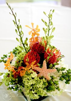 Tropical wedding centerpiece of hydrangea, pincushion protea, makara orchids, dendrobium orchids, hypericum berries, and starfish accents