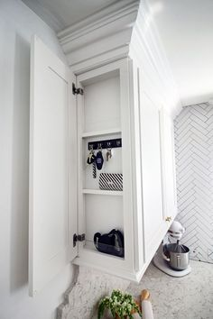 Martha Stewart Living™ Cabinetry with a secret panel for organizing your keys!! Genius!