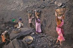People carry baskets of coal scavenged illegally at an open-cast mine in the village of Bokapahari in eastern India. AP photo