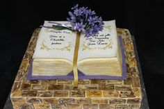 Custom cake - Book with message on top of brick wall, with agapanthus flower