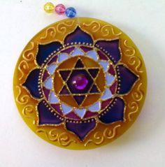 Mandala em acrílico de 10cm de diâmetro, pintura vitral, decorada com tinta relevo dourada e pedrinha colorida em ambos os lados. R$ 18,00