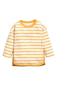 Katoenen trui: Een trui van zacht katoenen tricot met een bies in een contrasterende kleur rond de halsopening, langs de zijnaden en aan de onderkant. De trui heeft een borstzak en blinde drukknopen op één van de schouders.