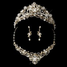 "Elegant and ornate, this bridal tiara and jewellery set features exquisite gold plating. The set features ivory freshwater pearls, clear rhinestones, and Swarovski crystals which coordinates beautifully with your white or ivory wedding dress.  Necklace - 14"" (Length) 2"" (Extender) Earrings - 1.75"""
