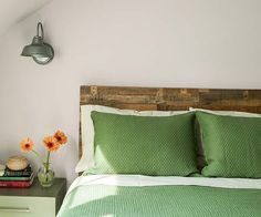 Sconces by Barn Light Electric flank a rustic wood pallet headboard in the master suite of this 1940s whole house remodel.