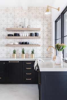 patterned backsplash, natural wood open shelves, black lower cabinets, brass hardware