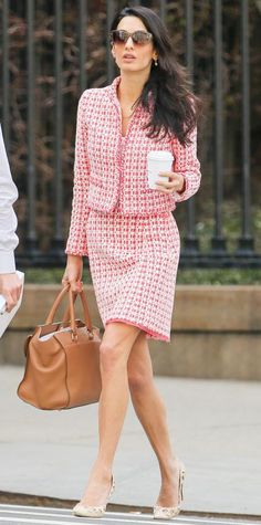 Amal Clooney wearing a pink tweed skirt set, with a caramel brown holdall and printed pumps.