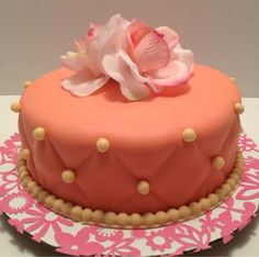 Cake with a flower on top with pearls you can eat and little diamond shapes