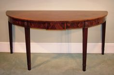 A fine late 18th Century figured mahogany demi-lune Console/Serving Table, having boxwood stung top above panelled frieze with central tablet, supported on stop fluted tapering legs with carved and beaded oval paterae. Circa: 1780