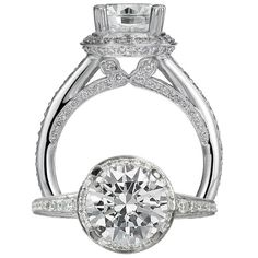 Modern engagement ring featuring a prong set round diamond centerstone surrounded by a double row micropavé basket and diamond pattern on the undergallery. This ring also features a graduated diamond shank.