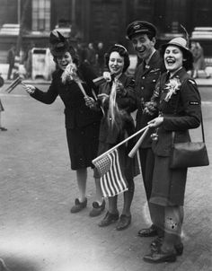 An RAF officer, two members of the Women's Royal Air Force and a civilian celebrate VE Day in London's Whitehall ~