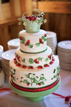 The luscious cake features a strawberry-filled basket on top and is trimmed with rich white-chocolate strawberries and delicate strawberry blossoms.