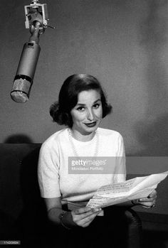 Italian TV announcer Nicoletta Orsomando (Nicolina Orsomando) sitting in a TV studios and reading a TV announcement. Rome, September 1957.