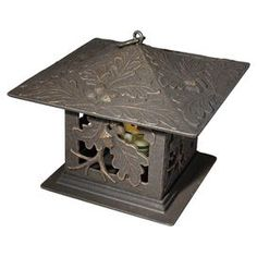 """Handmade recycled aluminum candle lantern in oil rubbed bronze with an oak leaf motif.  Product: LanternConstruction Material: Recycled aluminum and glassColor: BronzeFeatures:  Hand-paintedRust proofHand cast Accommodates: (1) Candle - not includedDimensions: 9.5"""" H x 9.5"""" W x 9.5"""" D"""